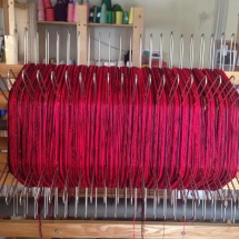 Red and black yarns on the loom